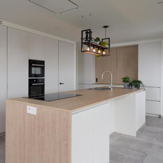 Strakke witte keuken met houten keukenblad